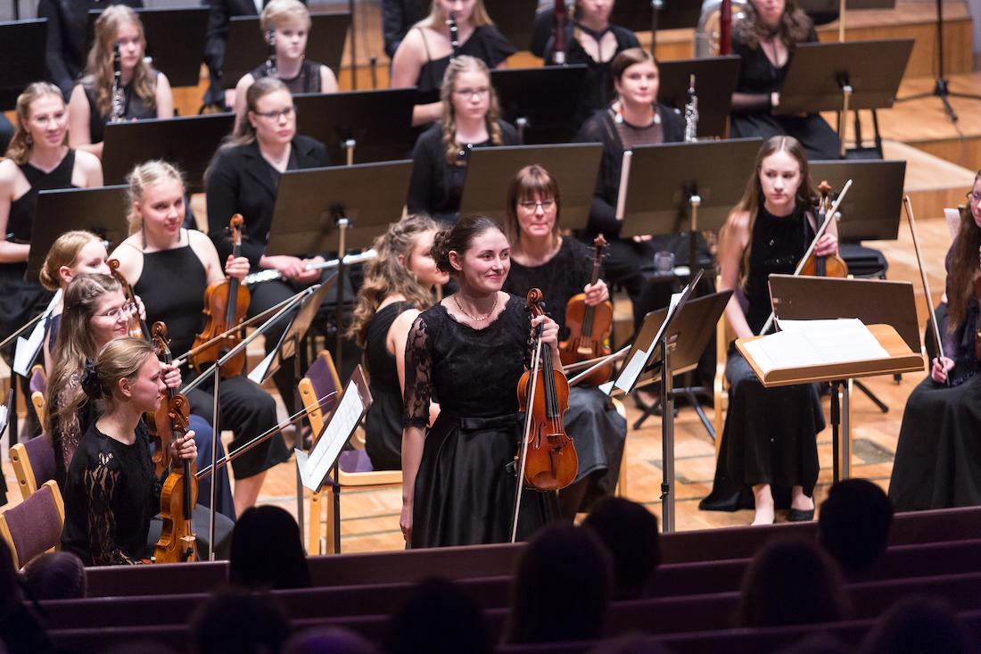 Viulisti esiintyy sinfoniaorkesterin kanssa
