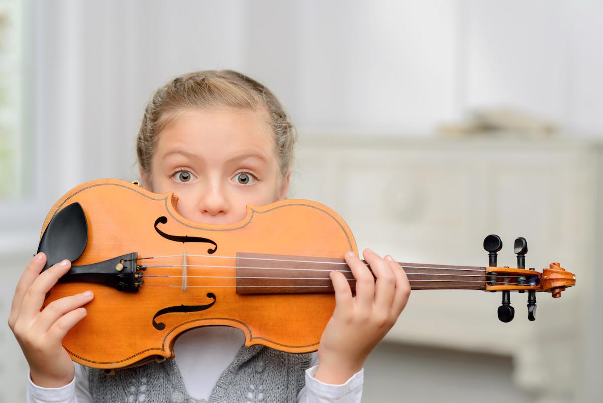 Iloinen tyttö pitelee viulua kasvojen edessä