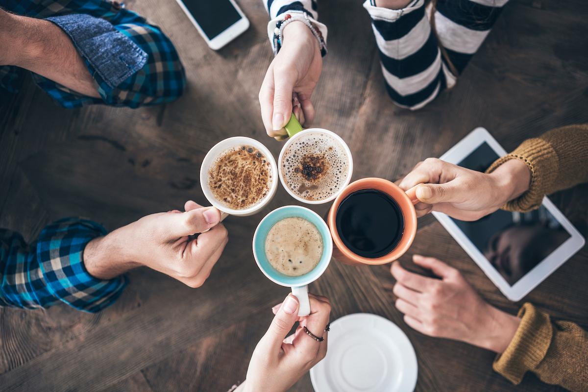 Neljä kahvinkuppia ja kahvinjuojaa