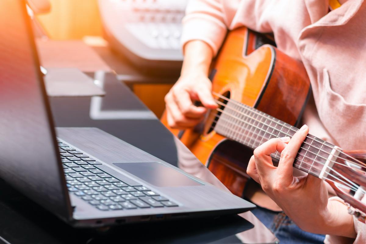 Mies opiskelee kitaransoittoa etänä
