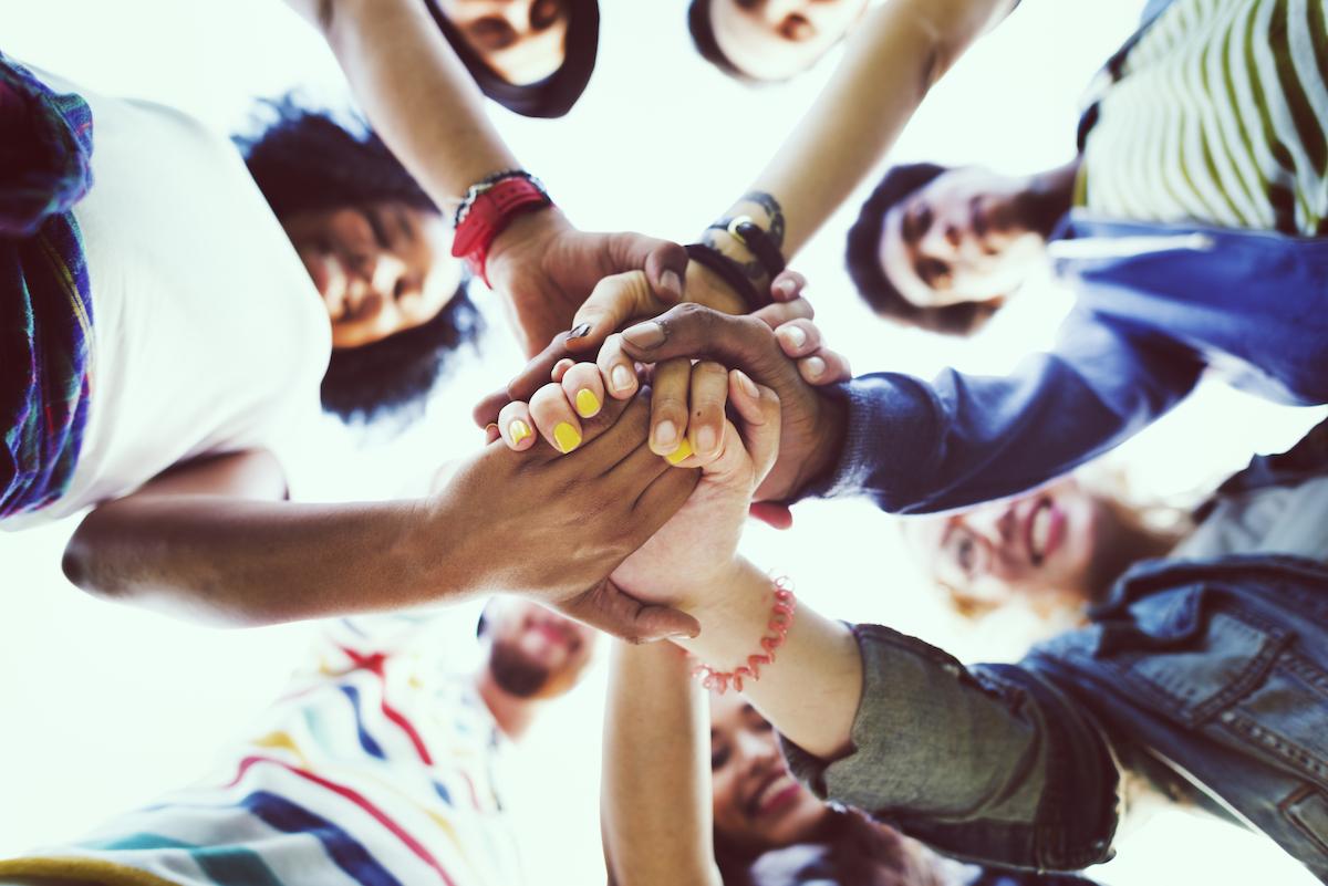 Nuoret pitävät käsiä toistensa päällä