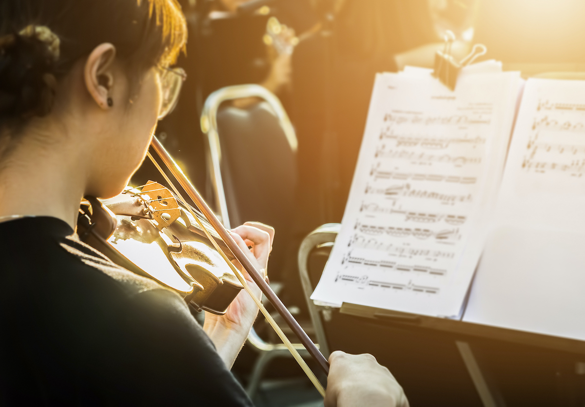 Nuori nainen soittaa viulua orkesterissa