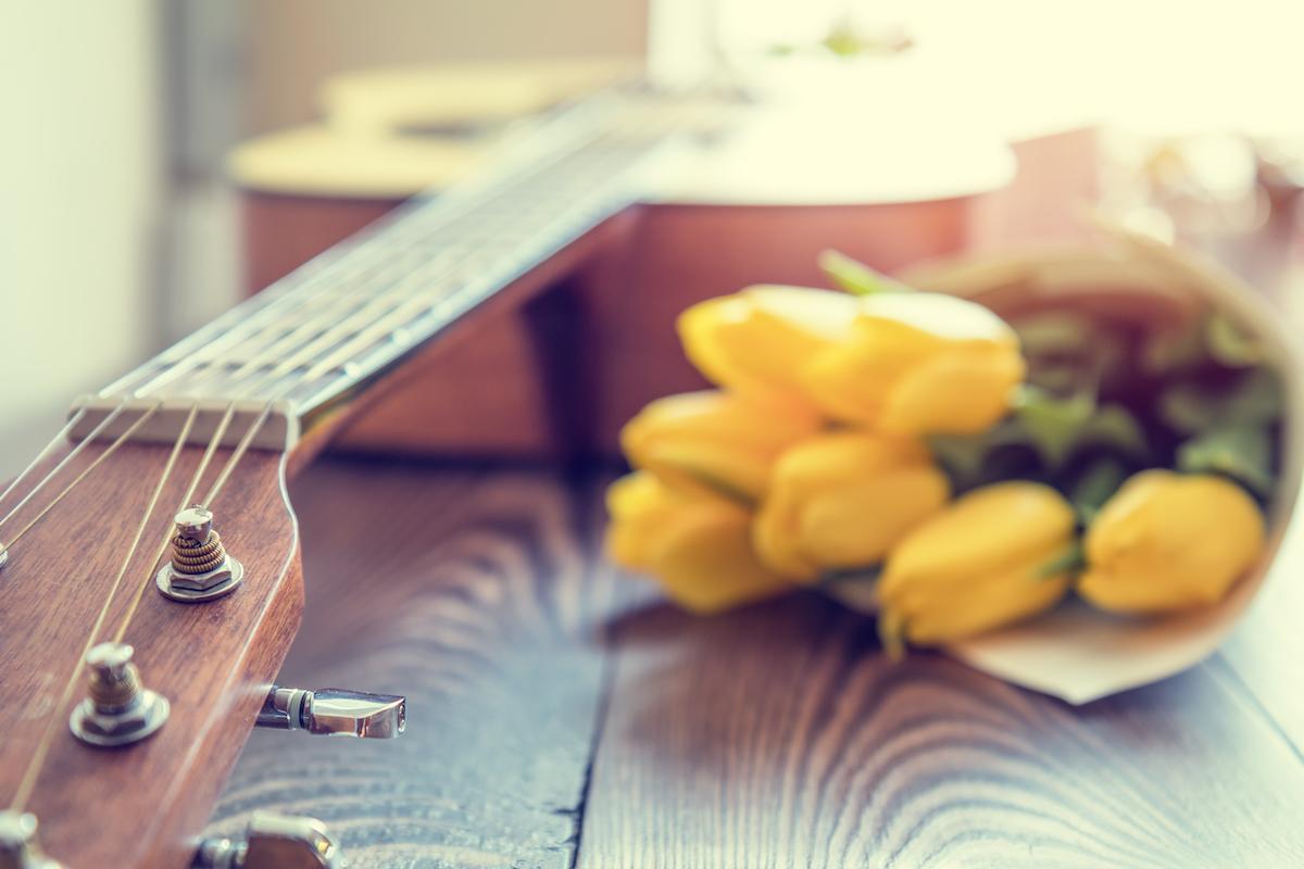 Akustinen kitara ja keltaiset tulppaanit pöydällä